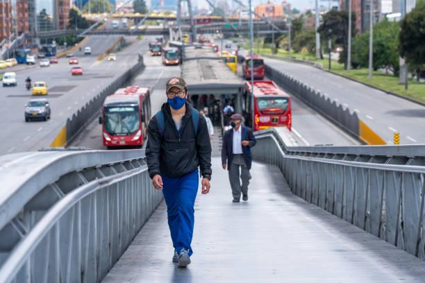Passanten verlassen am Mittag einen Busbahnhof mit einer Gesichtsmaske als Sicherheitsmaßnahme für die globale Coronavirus-Pandemie. – Foto