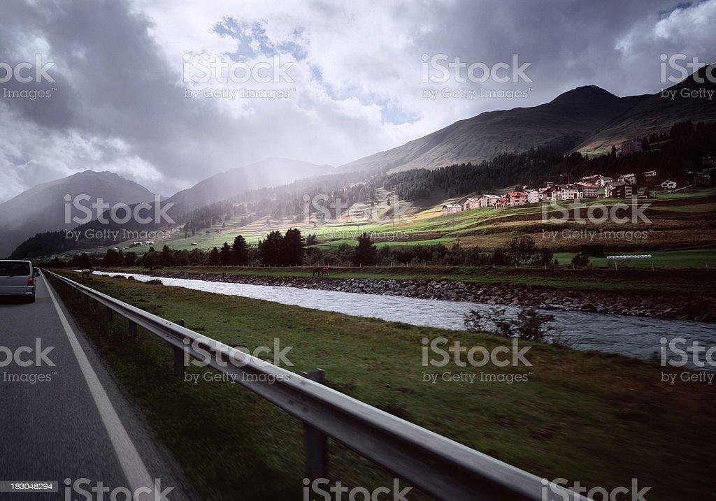 Passing an idyllic Swiss mountain landscape with village royalty-free stock photo