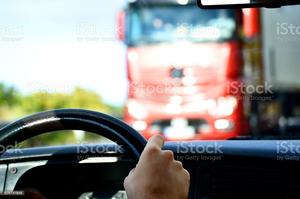 Passing by a red truck with a car stock photo