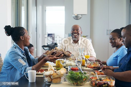 A multi-generational African ethnicity family eating together and a female passing the plate of barbequed meat to the senior malke at the head of the table Strand Cape Town South Africa