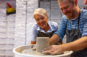 Senior woman and mature man smiling and talking while working on potters wheel making clay handmade craft in pottery workshop, friendship and guidance concept