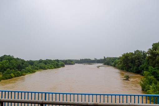 Passing over the bridge over river. The landscape of the river, the surface and the trees of the river's waterplain.