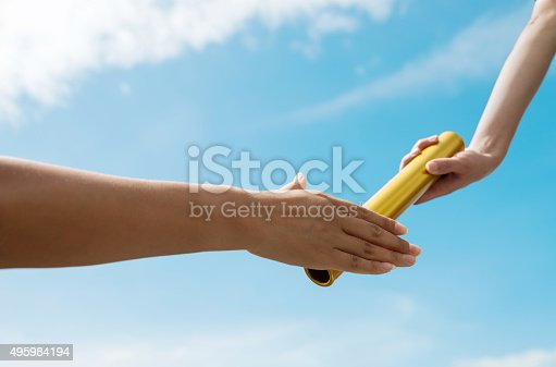 Two hands passing the baton for a relay race.