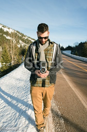Shot of young man in warm clothing taking photos with retro camera outdoors on the road during winter