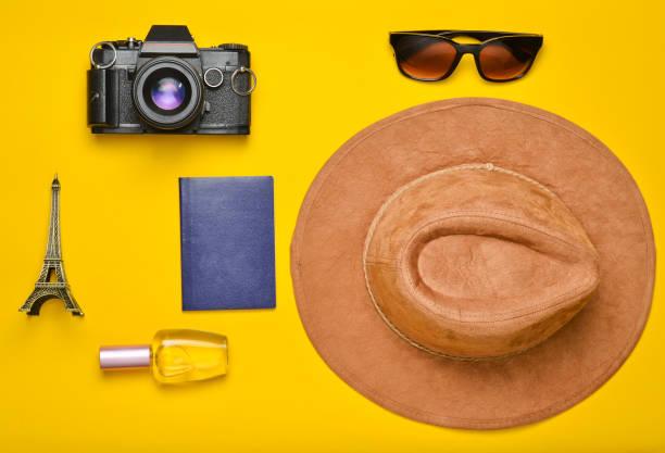 passion pour les voyages, le concept de nostalgie. voyage en france, paris. ressenti photo argentique, lunettes, passeport, bouteille de parfum, chapeau, statuette de souvenir de la présentation de la tour eiffel sur un fond de papier orange - camera sculpture photos et images de collection