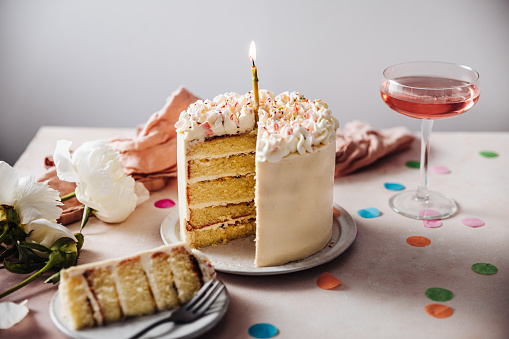 Homemade layered cake decorated with cheese cream icing and multi colored sugar sprinkles. Beautiful birthday cake with candle on a table.