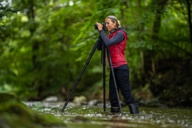passion, hobby, occupation, female photographer working outdoors in river stock photo