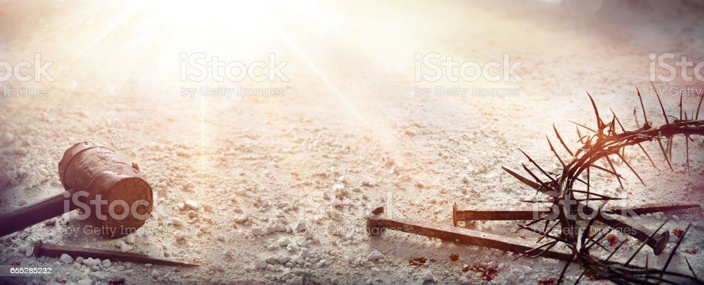 Passion Of Jesus Christ - Hammer and Bloody Nails And Crown Of Thorns On Arid Ground royalty-free stock photo