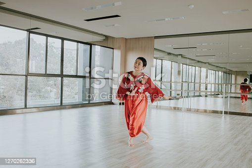 Young at heart of Thai beautiful senior enjoy showing and resting with classical Thai dance at home, Bangkok Thailand