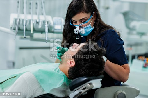 A dentist performing a dental procedure on a patient