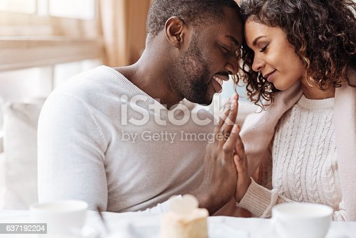 istock Passionate African American couple touching hands in the cafe 637192204