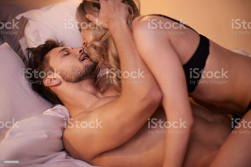Passionate couple in the bedroom stock photo