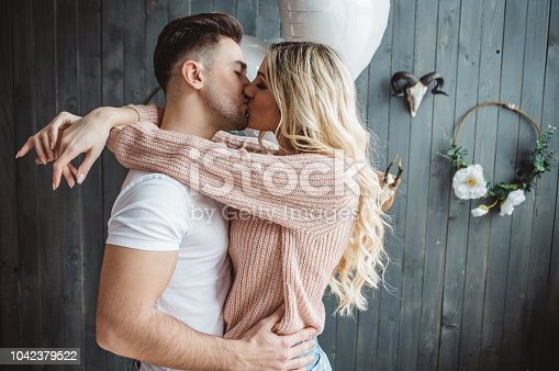 Couple on Valentine day enjoy in love. They are in bedroom, having romantic moment together embracing, kissing and smiling