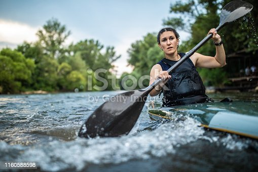 Portrait of Strong sport woman kayaking on speed river , holding oar and enjoying sport training