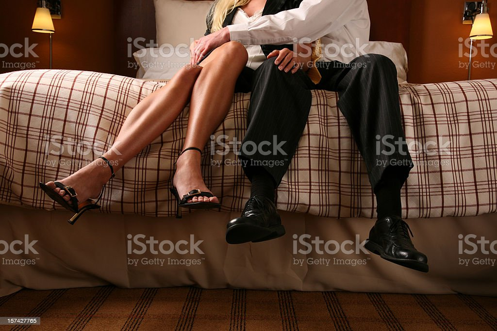 Passionate Lovers Sitting on Edge of Bed Touching Legs Hugging stock photo