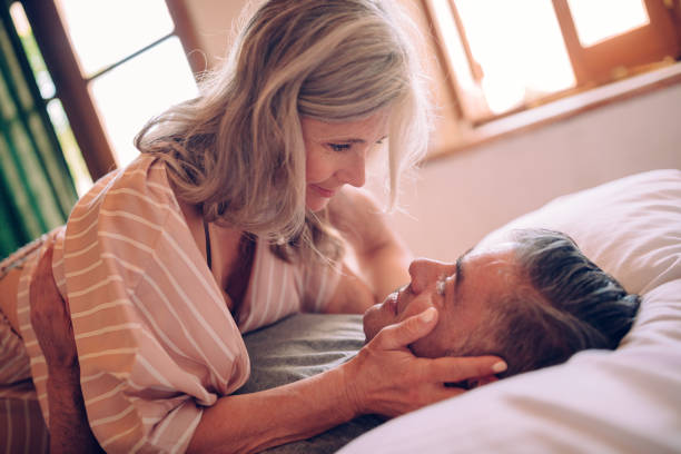 Passionate mature couple flirting while lying down in bed stock photo