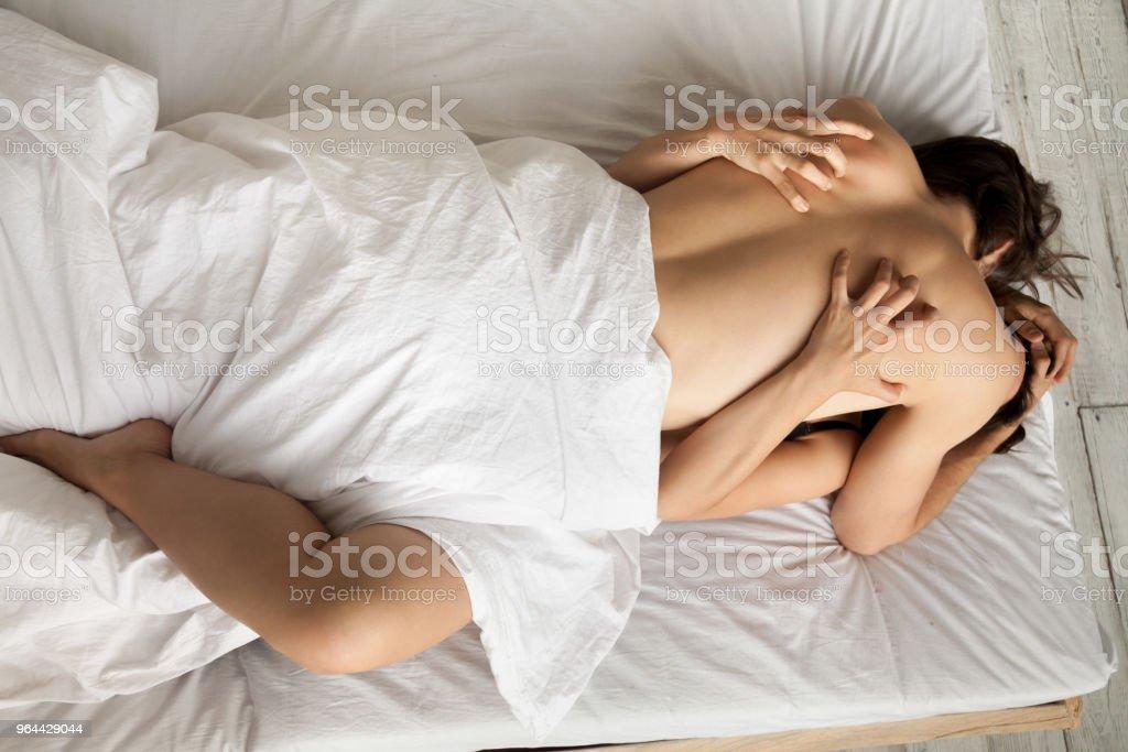 Gepassioneerde sensuele liefhebbers genieten van het maken van liefde op bed, top uitzicht - Royalty-free Aanhankelijk Stockfoto