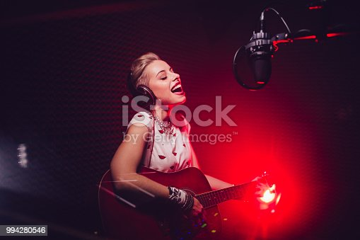 Fashionable hipster music artist playing the guitar and recording song in professional music studio