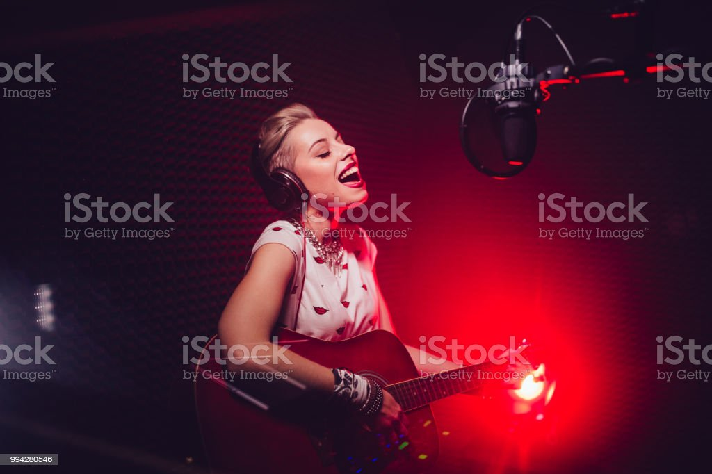 Passionate singer playing the guitar and recording song in studio stock photo