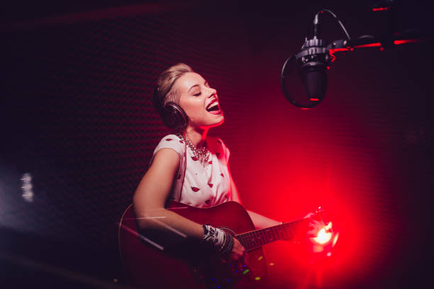 Passionate singer playing the guitar and recording song in studio Fashionable hipster music artist playing the guitar and recording song in professional music studio singer stock pictures, royalty-free photos & images