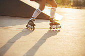 Low section of teenage girl roller skating in skateboard park on sunset. The sun is shining and makes shadows on the concrete. Roller skater girl is wearing long socks, and has a plaid shirt tied around her waist.