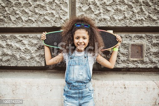 Girl on street enjoy in beautiful day and have fun on longboard. She holding longboard on shoulders and smiling