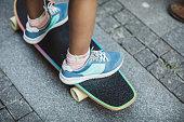 Crop shot of girls feet riding longboard.