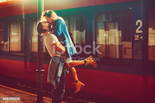 istock Passionate young man and woman kissing beside the train at the railway station 946480528