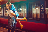Passionate young man and woman kissing beside the train at the railway station. The shot is executed with available natural light, and the copy space has been left.
