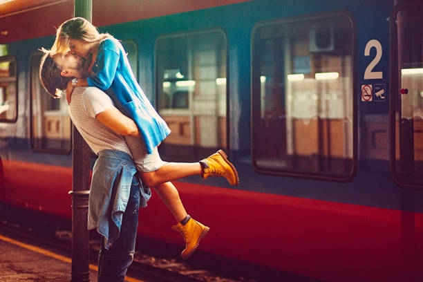 Passionate young man and woman kissing beside the train at the railway station stock photo