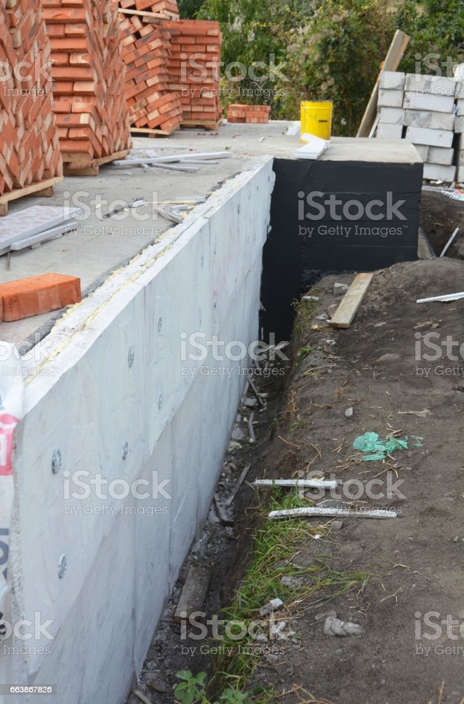 Passive house foundation insulation with polystyrene foam boards for House Energy Saving and Energy Efficiency. Damp proofing Coatings.Waterproofing house foundation with spray on tar. stock photo