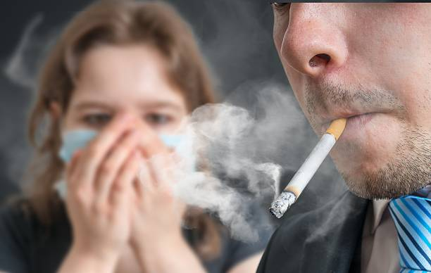 Passive smoking concept. Man is smoking cigarette. Passive smoking concept. Man is smoking cigarette and woman is covering her face. A lot of smoke around. smoking issues stock pictures, royalty-free photos & images