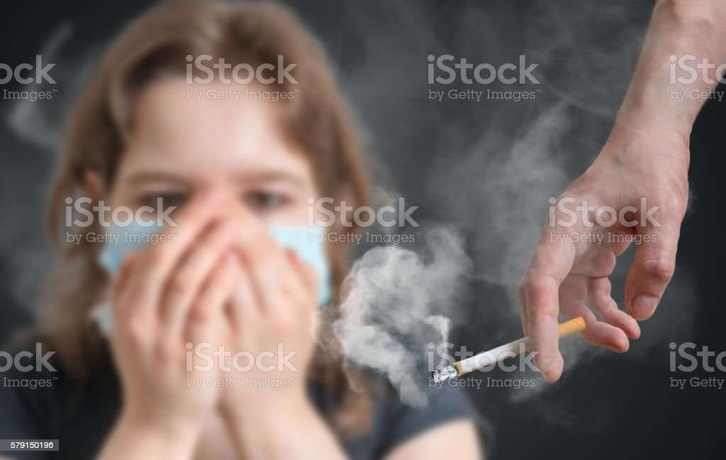Passive smoking concept. Woman is covering face from cigarette smoke. stock photo