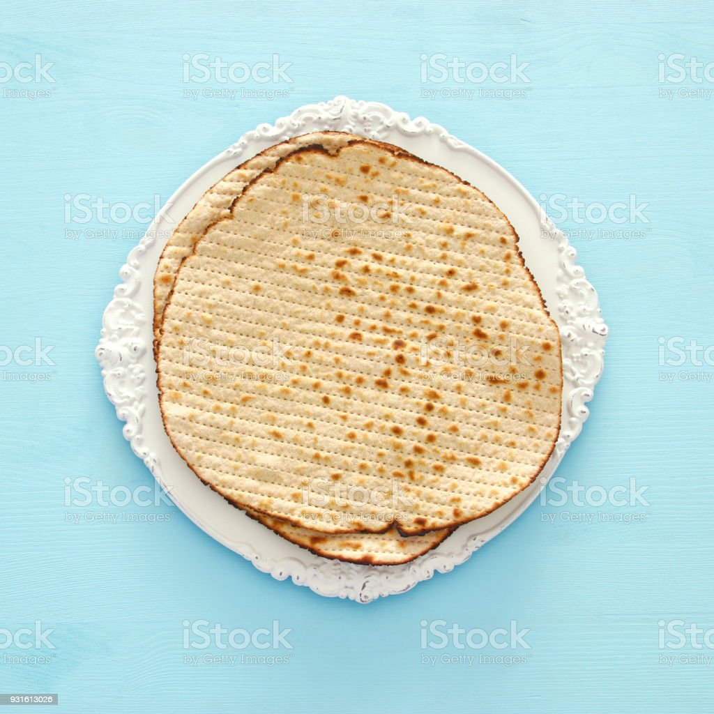 passover background with matzoh over light blue wooden background. stock photo