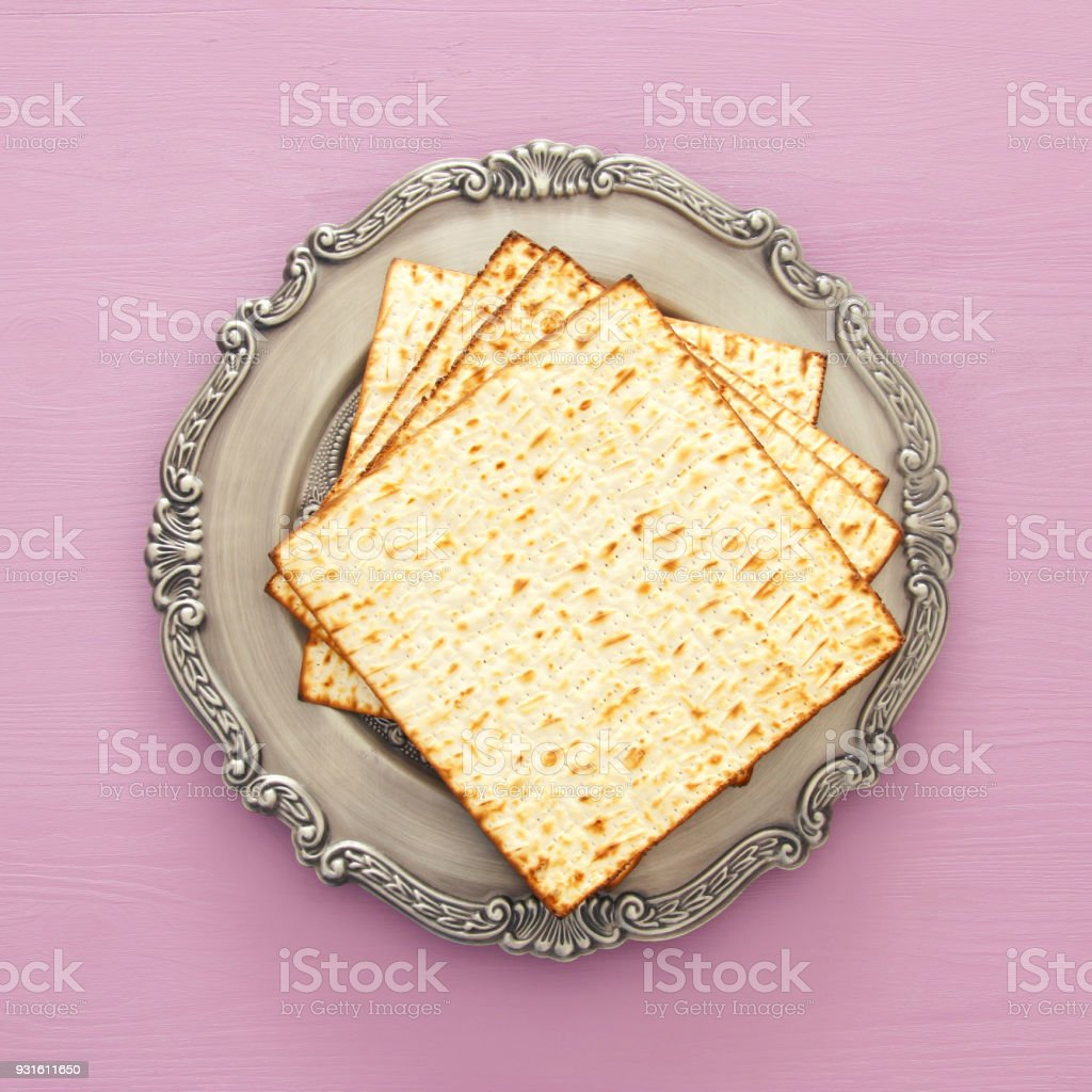 passover background with matzoh over light purple wooden background. stock photo