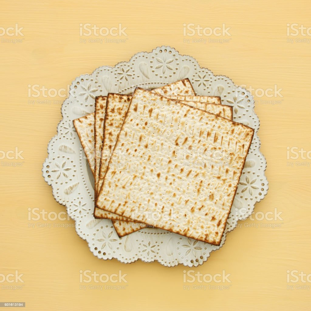 passover background with matzoh over yellow wooden background. stock photo