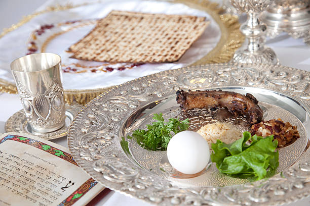 Passover food on silver plate on table Traditional symbols on a seder plate for the Jewish festival of Passover. seder plate stock pictures, royalty-free photos & images