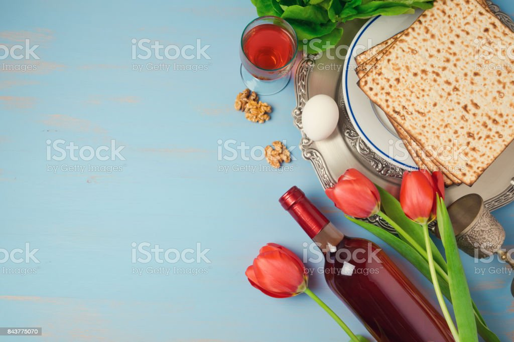 Passover holiday concept seder plate, matzoh and tulip flowers on wooden background. Top view from above stock photo