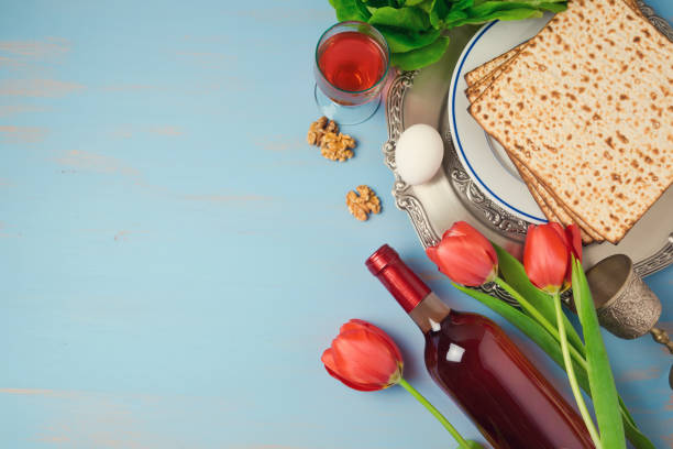 passover holiday concept seder plate, matzoh and tulip flowers on wooden background. top view from above - passover stock photos and pictures