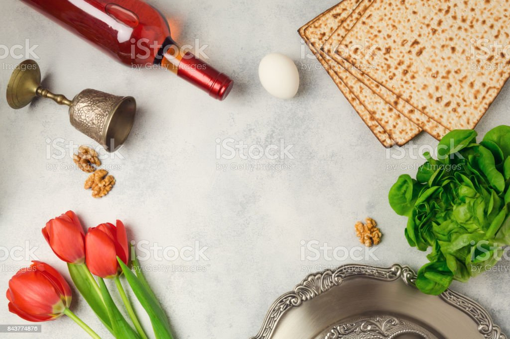 Passover holiday concept seder plate, matzoh and wine bottle on bright background. Top view from above stock photo