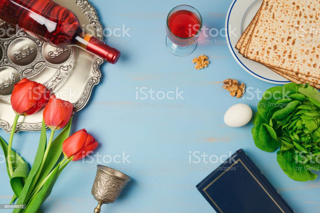 Passover holiday concept seder plate, matzoh, tulip flowers and wine bottle on wooden background. Top view from above stock photo