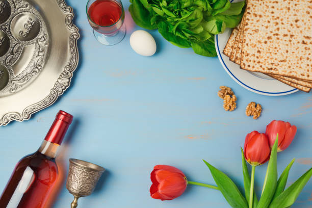 passover holiday concept seder plate, matzoh, tulip flowers and wine bottle on wooden background. top view from above - passover stock photos and pictures