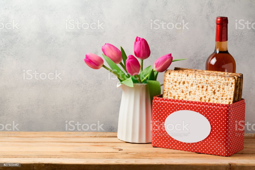 Passover holiday concept with wine bottle, matzoh and tulip flowers over bright background stock photo