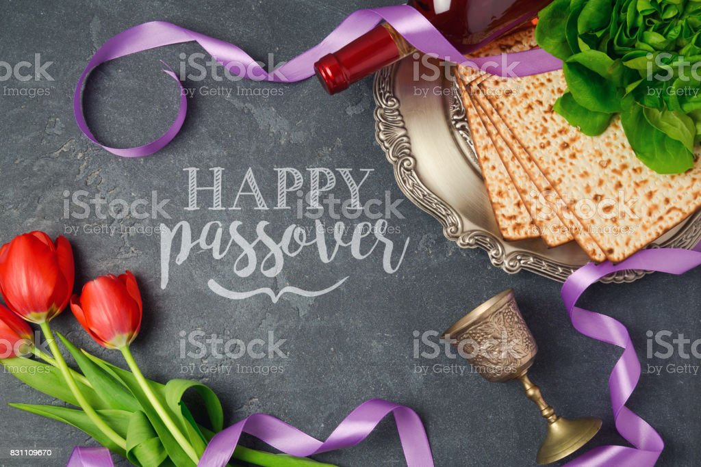 Passover holiday greeting card matzoh and tulip flowers on dark background. Top view from above stock photo