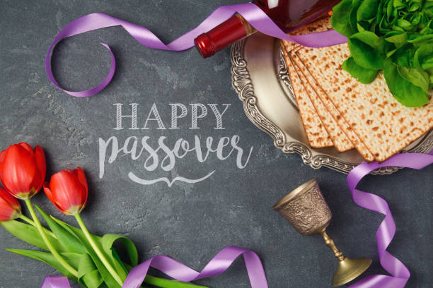 passover holiday greeting card matzoh and tulip flowers on dark background. top view from above - passover stock photos and pictures