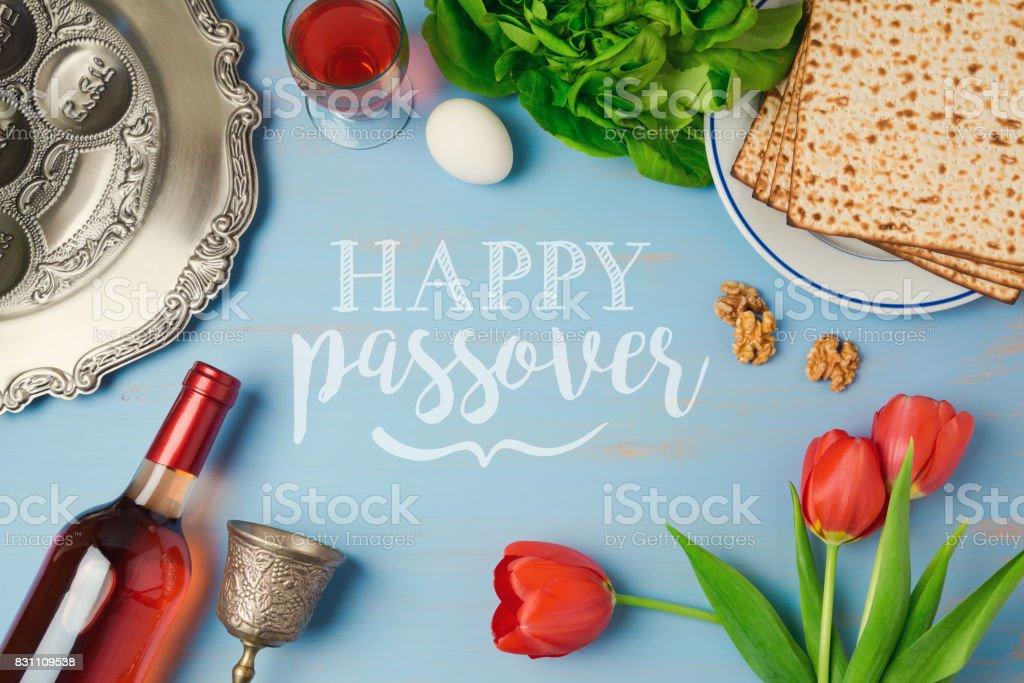 Ostern Urlaub Grusskarte mit Seder Platte Matzoh, Tulpen und Blumen Weinflasche auf hölzernen Hintergrund. Draufsicht von oben – Foto