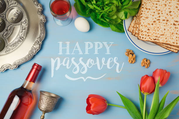 Passover holiday greeting card with seder plate, matzoh, tulip flowers and wine bottle on wooden background. Top view from above Passover holiday greeting card with seder plate, matzoh, tulip flowers and wine bottle on wooden background. Top view from above passover stock pictures, royalty-free photos & images