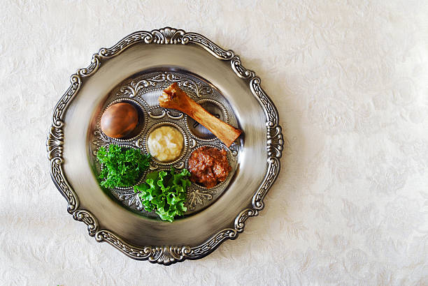 Passover seeder plate seen from above on light background Traditional symbols on a seder plate for the Jewish festival of Passover.  seder plate stock pictures, royalty-free photos & images