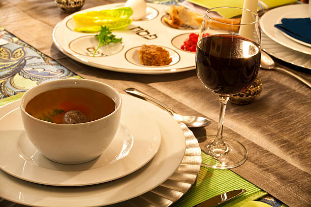 """Passover Table Setting """"Seder plate, glass of wine and a bowl of Mazto ball soup provide the setting at a passover table."""" seder plate stock pictures, royalty-free photos & images"""