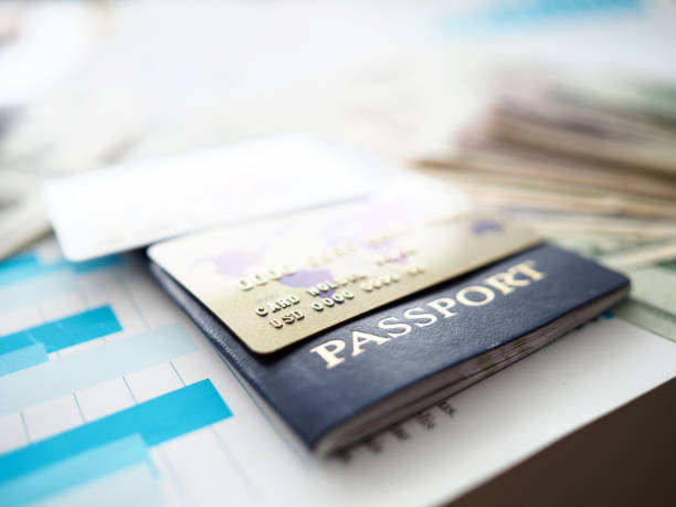 Passport and plastic cards in USD lying on financial report document stock photo